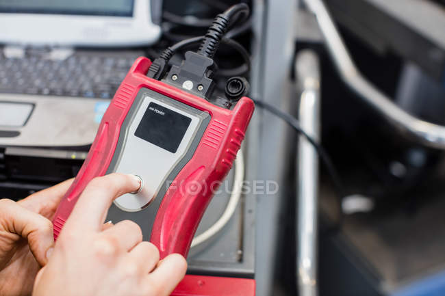 Hands of female mechanic using electronic diagnostic device in repair garage — Stock Photo