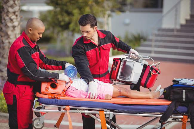 Sanitäter versorgen verletztes Mädchen am Unfallort mit Sauerstoff — Stockfoto