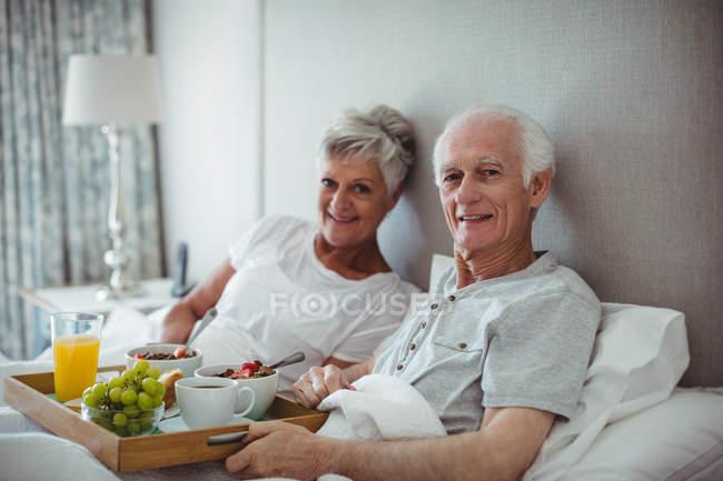 Senior pareja con desayuno en cama en camas - foto de stock