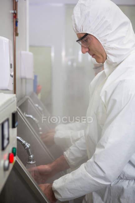 Техники мыли руки в раковине для мытья рук на мясокомбинате — стоковое фото
