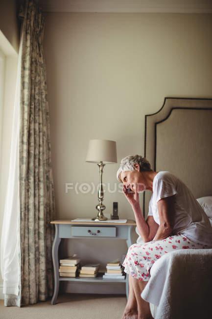 Mujer mayor preocupada con la cabeza en las manos sentada en el dormitorio - foto de stock
