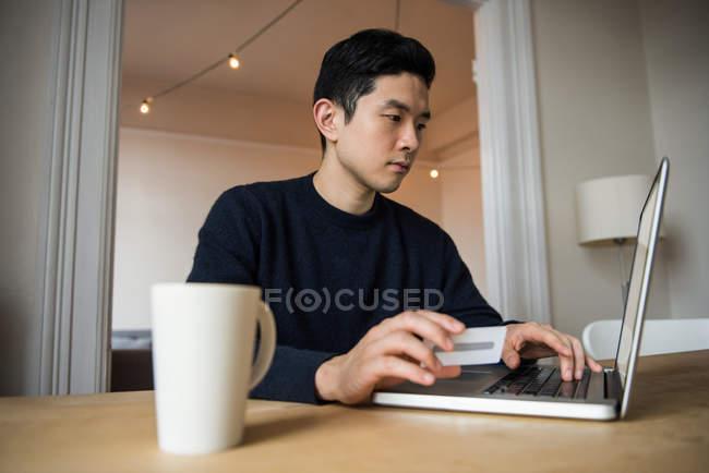 Uomo che fa shopping online su computer portatile a casa — Foto stock