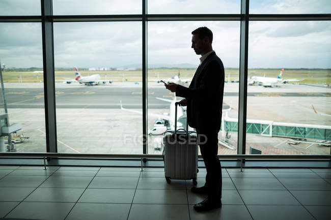 Businessman with luggage using mobile phone at airport — Stock Photo