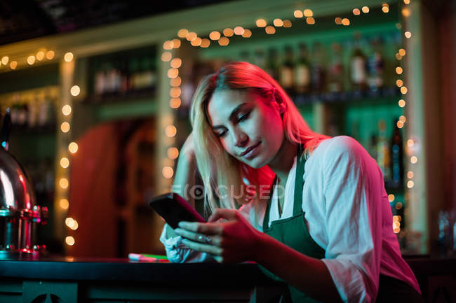 Waitress using her mobile phone at the bar counter — Stock Photo