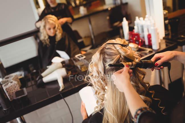 Женский парикмахер, укладка волос клиентов в салоне — стоковое фото