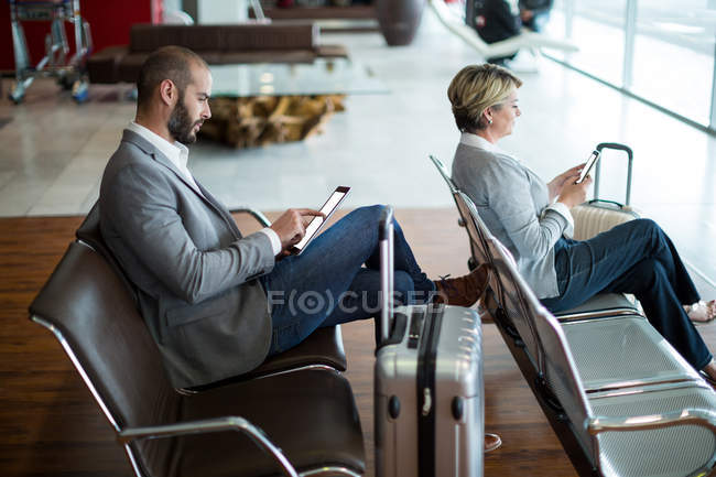 Business people using digital tablet and mobile phone in waiting area at airport terminal — Stock Photo