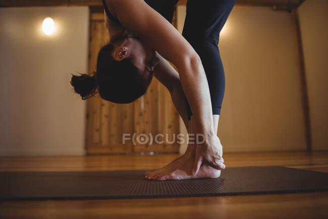 Женщина практикующих йогу согнуть в фитнес-студии — стоковое фото