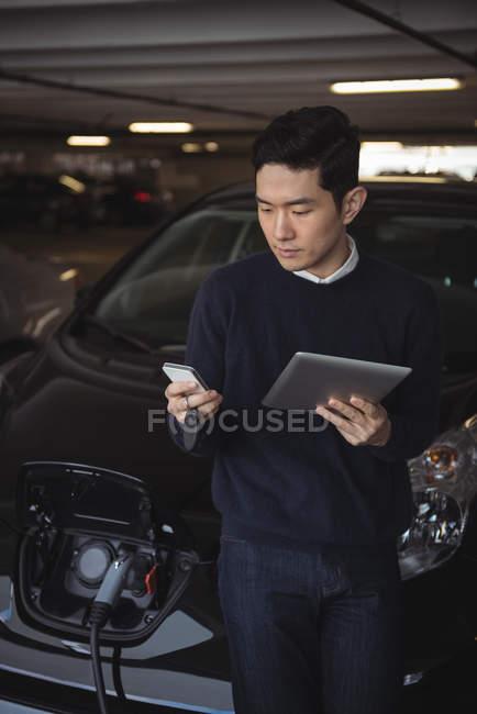 Homme à l'aide de tablette numérique et téléphone mobile pendant le chargement de la voiture électrique dans garage — Photo de stock