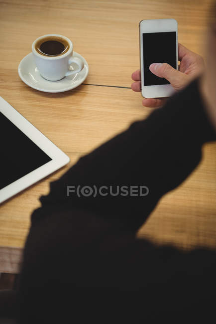 Cropped view of man using his phone while sitting in coffee shop — Stock Photo