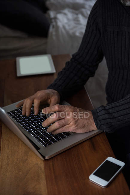 Milieu de la section de l'homme assis à la table et en utilisant un ordinateur portable à la maison — Photo de stock
