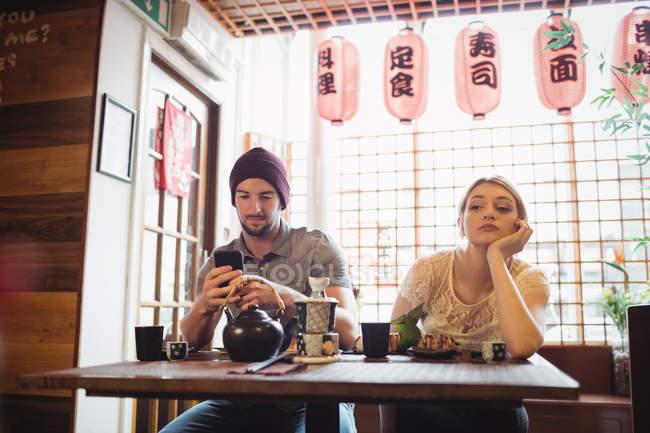 Homem ignorando mulher enquanto fala ao telefone no restaurante — Fotografia de Stock