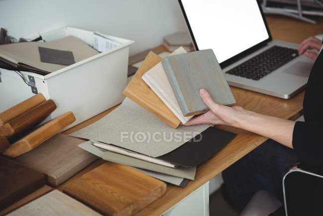 Mid section of business executive holding stone slabs and using laptop in office — Stock Photo