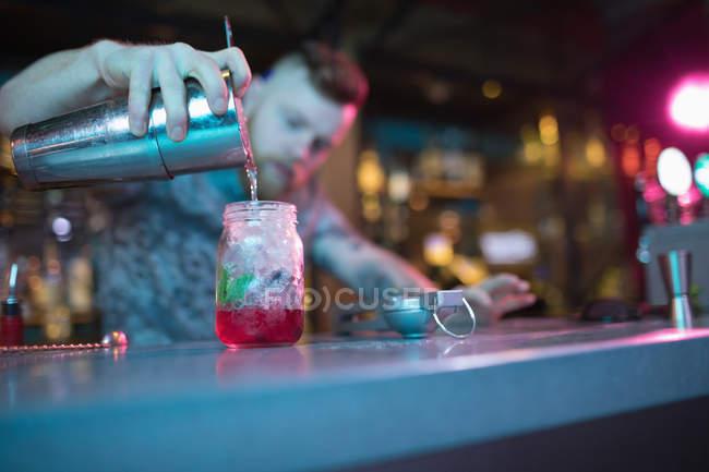 Bar préparant un cocktail au comptoir dans le bar — Photo de stock