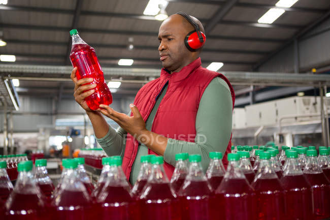 Serious male worker wearing protective ear-wear while inspecting bottle in factory — Stock Photo