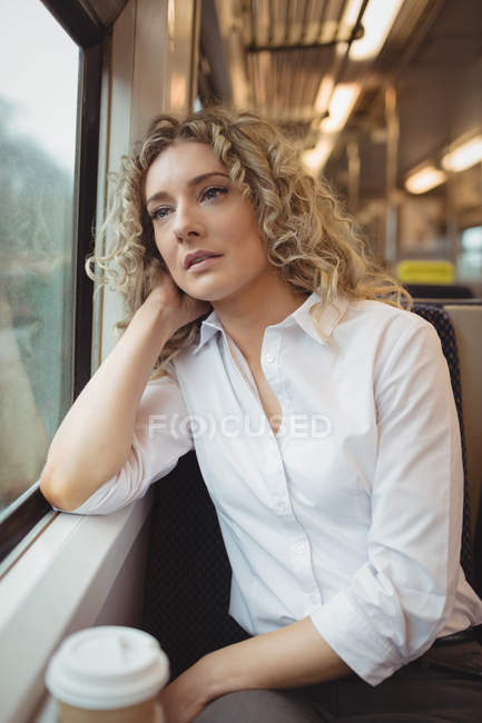 Thoughtful businesswoman looking through window while travelling — Stock Photo