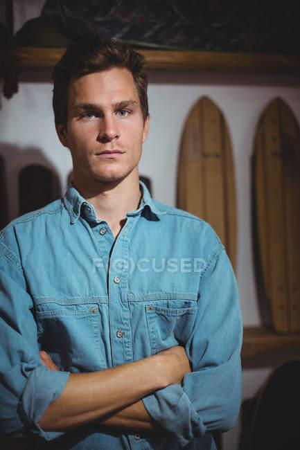 Joven confiado parado en la tienda de tablas de surf - foto de stock