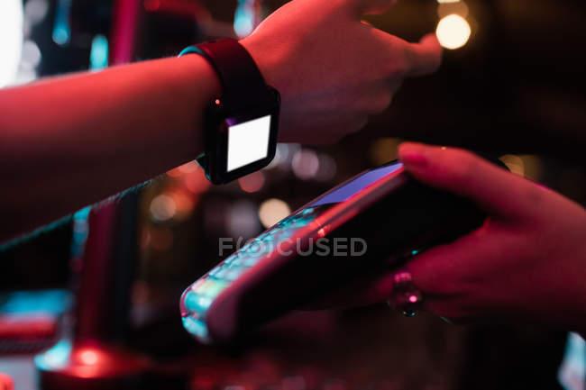 Client d'effectuer le paiement par l'intermédiaire de smart montre en bar — Photo de stock