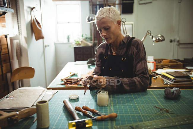 Attentive craftswoman preparing leather belt in workshop — Stock Photo