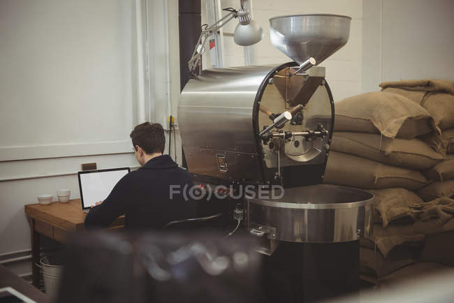 Man using laptop while sitting besides coffee roasting machine in coffee shop — Stock Photo