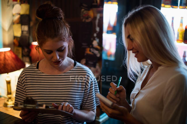Kellnerin, die Diskussion über das Menü mit Frau in der bar — Stockfoto