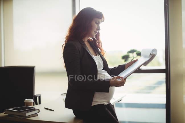 Беременная деловая женщина читает бумажные документы в офисе — стоковое фото
