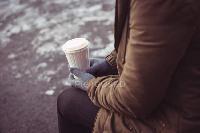 Крупный план женщины с одноразовой чашкой кофе на берегу реки зимой — стоковое фото