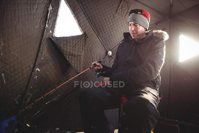 Pescador de hielo comprobando caña de pescar - foto de stock