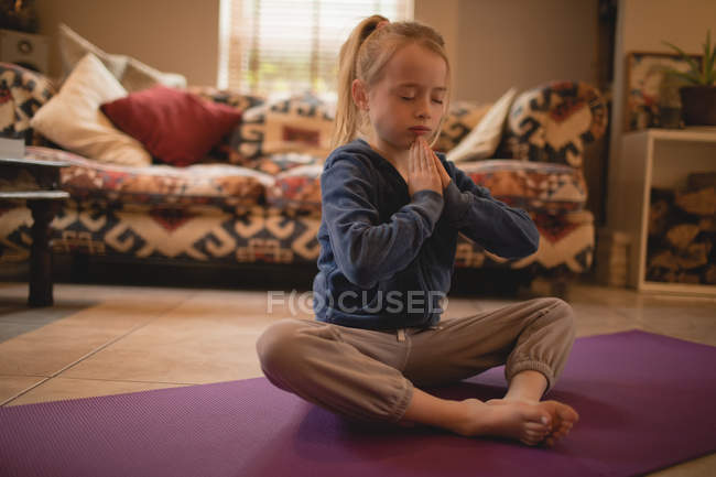 Fille effectuer du yoga dans le salon à la maison — Photo de stock