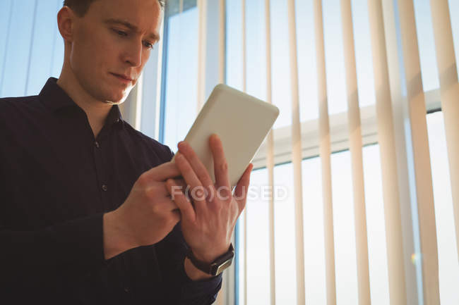 Male executive using digital tablet near window blinds in office — Stock Photo