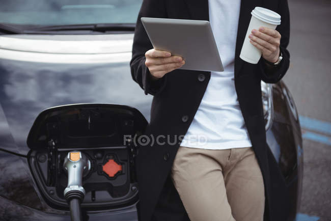 Mittleren Bereich des Mannes mit digital-Tablette während des Ladevorgangs Auto Elektrofahrzeug Ladestation — Stockfoto