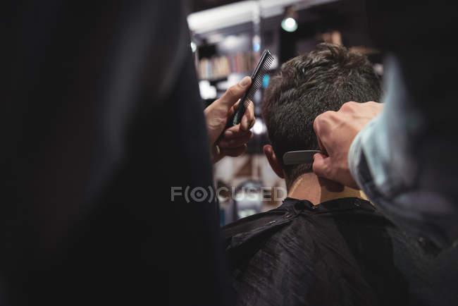 Мужчина стрижется парикмахером с бритвой в парикмахерской — стоковое фото