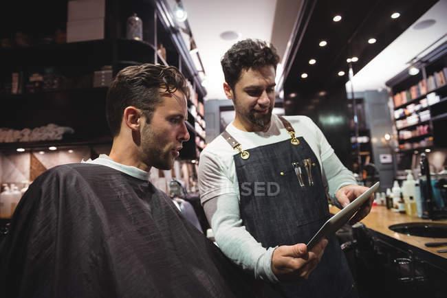 Barbiere che mostra l'acconciatura al cliente su tablet digitale in barbiere — Foto stock