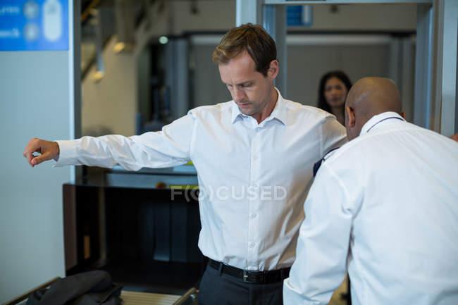 Oficial de seguridad del aeropuerto usando un detector de metales de mano para comprobar un viajero en el aeropuerto - foto de stock