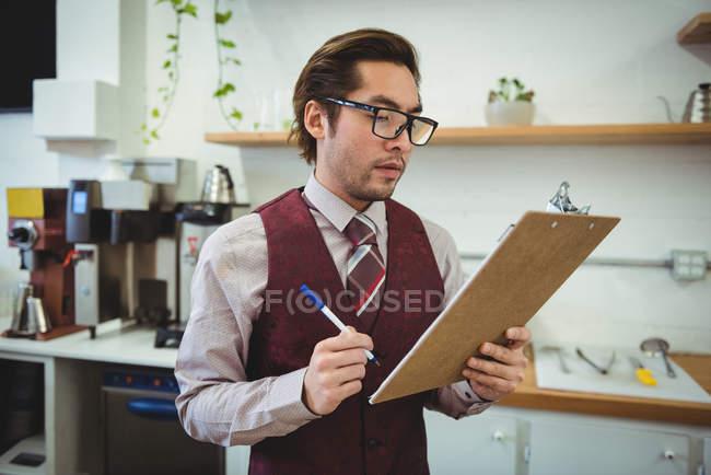 Hombre escribir con lápiz en el portapapeles en cafetería - foto de stock