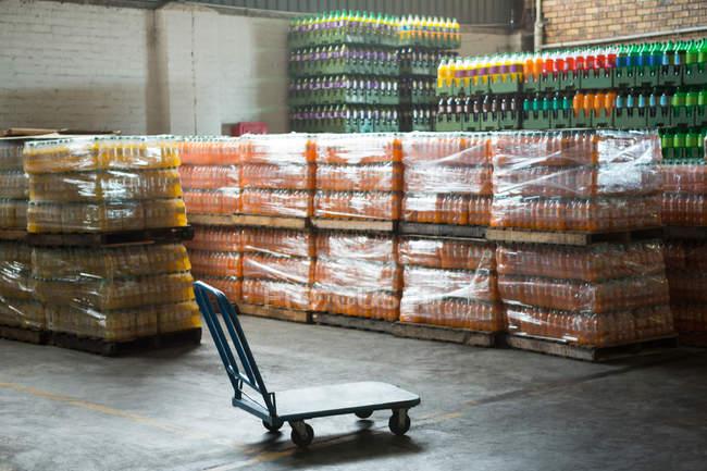 Пустой тележки и упакованные бутылки сока расположены на складе — стоковое фото