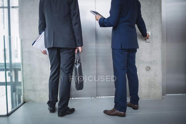 Faible section des hommes d'affaires permanent par l'ascenseur et appuyez sur la touche au bureau — Photo de stock