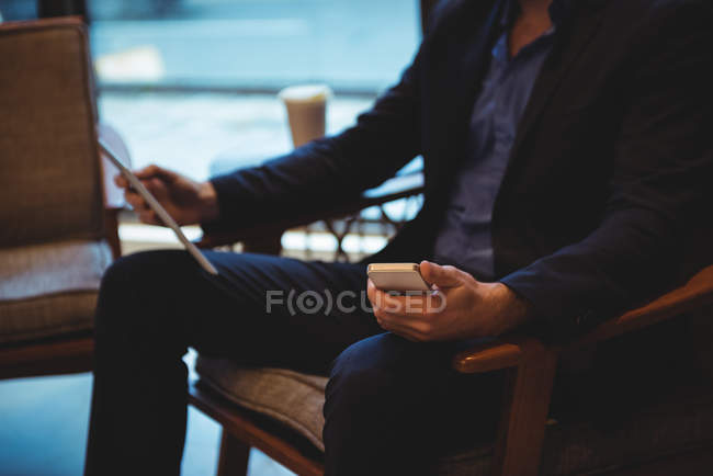 Mid section of businessman using mobile phone and digital tablet in cafe — Stock Photo