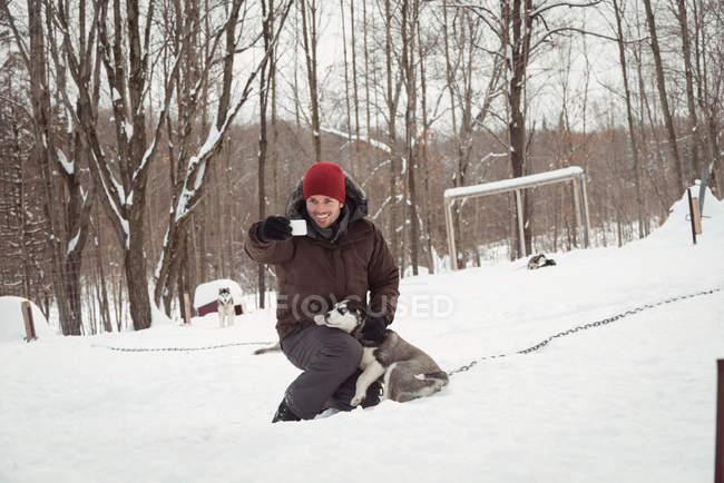 Uomo che prende selfie con husky siberiano durante l'inverno — Foto stock