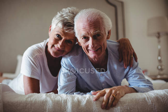 Portrait of happy senior couple lying on bed in bed room — Stock Photo