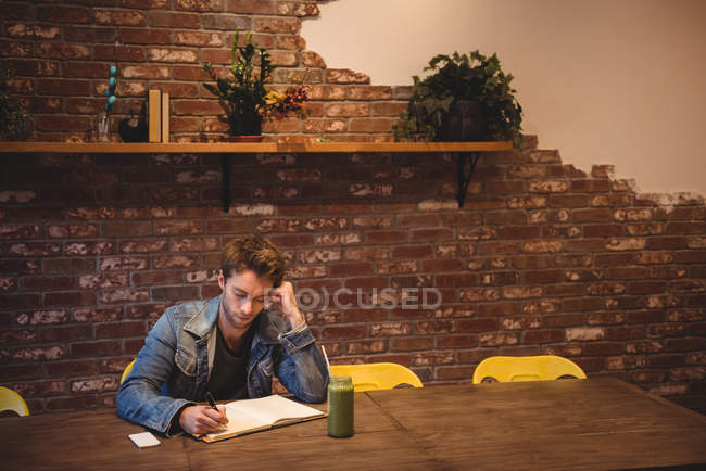 Man writing in notebook dairy in a cafe — Stock Photo