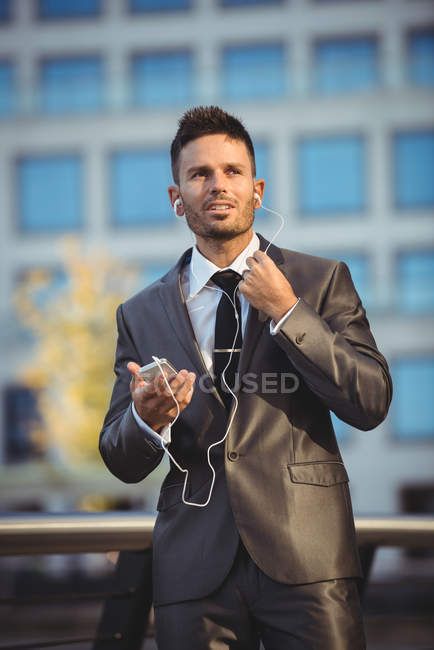 Businessman listening to music on mobile phone near office building — Stock Photo