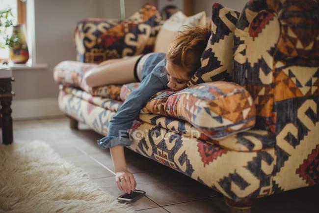 Frau benutzt Handy, während sie zu Hause auf dem Sofa liegt — Stockfoto