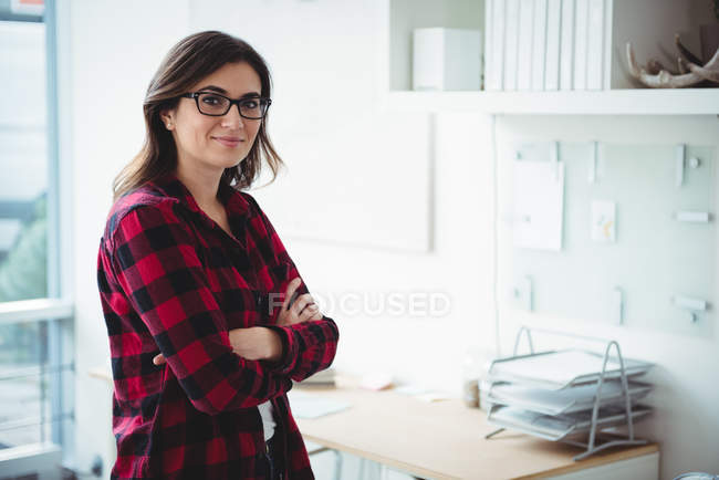 Portrait of smiling business executive standing with arms crossed in office — Stock Photo