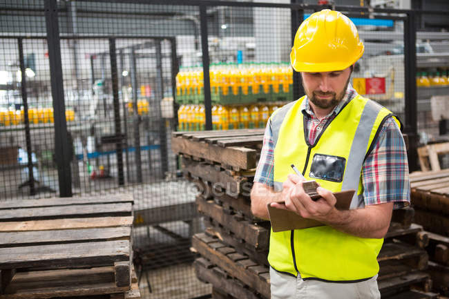 Confident male worker noting about products in warehouse — Stock Photo