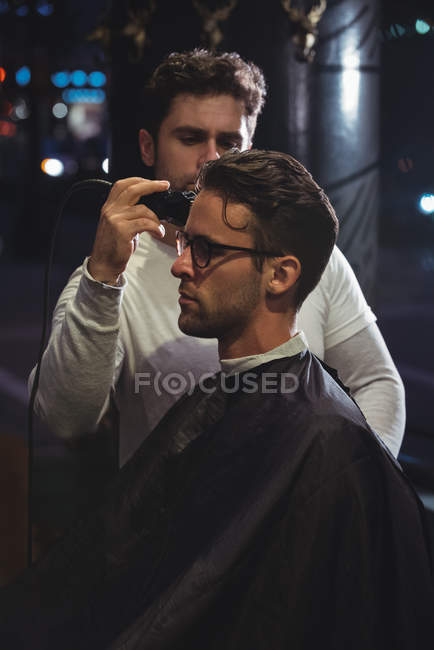 Man getting hair trimmed by hairdresser with trimmer in barber shop — Stock Photo