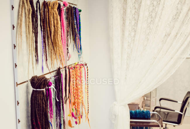 Assorted colourful artificial dreadlocks in shop — Stock Photo