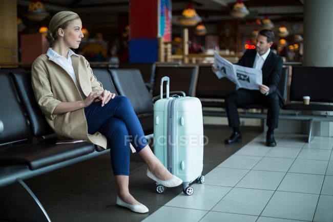Pensativo viajero femenino esperando en la sala de espera en el aeropuerto - foto de stock