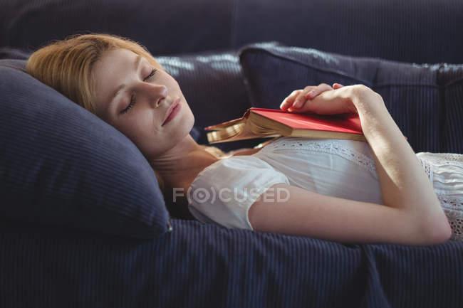 Mulher bonita relaxando no sofá na sala de estar em casa — Fotografia de Stock