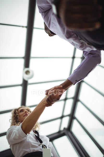Vue faible angle de dirigeants d'entreprise se serrant la main au corridor de bureau — Photo de stock