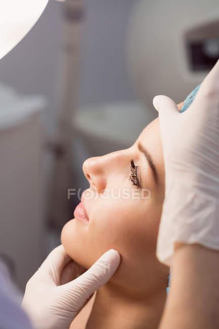 Hände des Arztes untersuchen weibliches Gesicht für kosmetische Behandlung in Klinik — Stockfoto